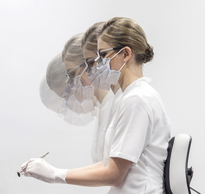 Dentist wearing loupes and a face mask