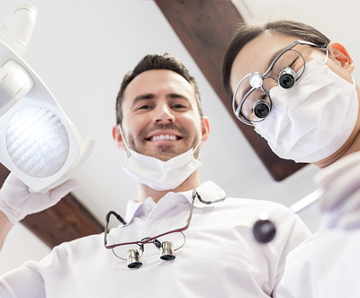 Dentist and assistant with loupes looking down into camera