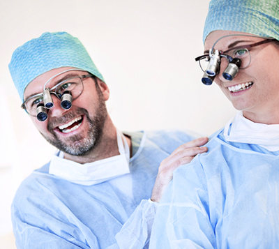 Two dentists wearing loupes and laughing
